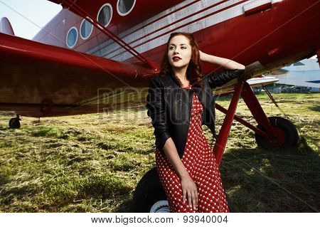 pin-up female sitting on wheel in dress and jacket