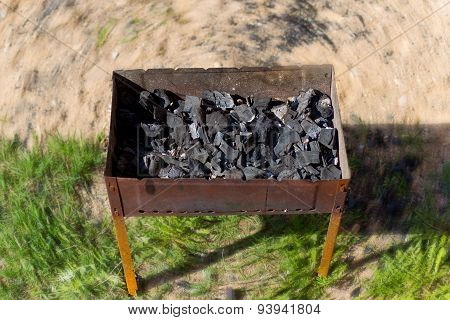 burning wood in an open charcoal grill, coals in the brazier
