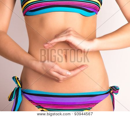 Woman in bikini with hands on her stomach