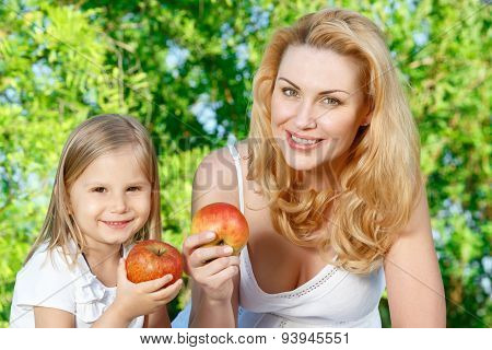 Mother and daughter sitting on cover with apples
