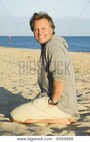 Happy smiling forties man sitting on beach