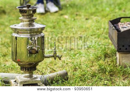 Picnic on the grass with a samovar and meat