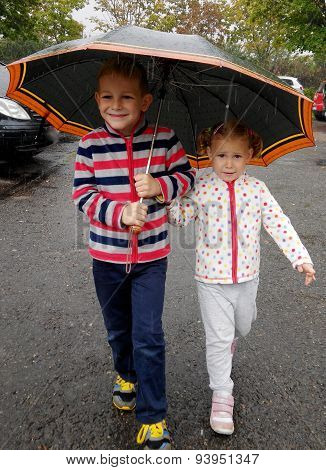 Little Brother And Sister Under Umbrella In Rain