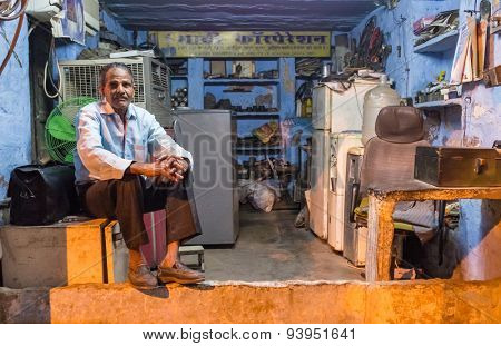 JODHPUR, INDIA - 10 FEBRUARY 2015: Elderly electrician sits on fridge before closing refrigerator service shop.