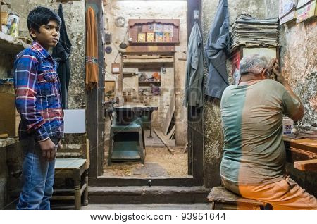 JODHPUR, INDIA - 10 FEBRUARY 2015: Young  apprentice awaits instructions while carpenter works. Children are used as cheap labourers through out Asia.