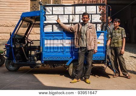 JODHPUR, INDIA - 10 FEBRUARY 2015: Men stand next to delivery three-wheeler with cargo in the back.
