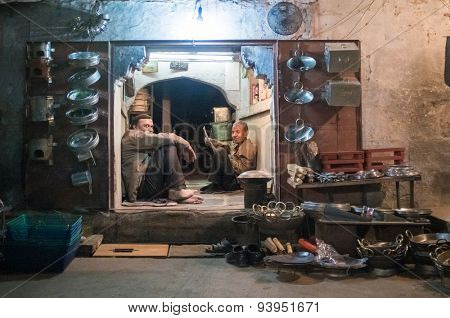 JODHPUR, INDIA - 16 FEBRUARY 2015: Two workers sit and rest before closing time. Stores with kitchen pottery and other products made from metal are common on Asian markets.