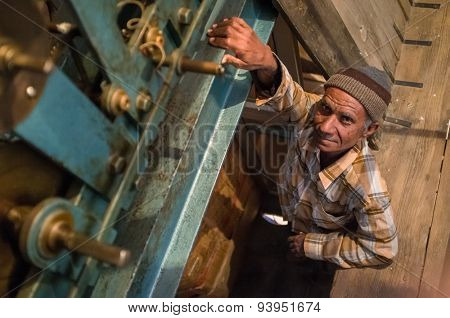 JODHPUR, INDIA - 11 FEBRUARY 2015: Ghanta Ghar clock man stands next to clock mechanism inside tower.