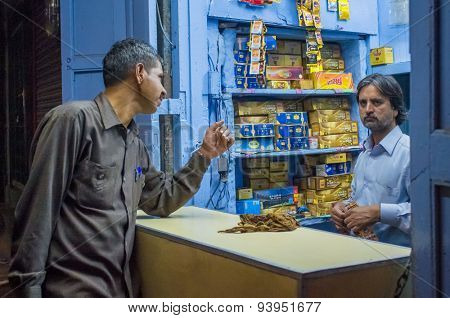 JODHPUR, INDIA - 16 FEBRUARY 2015: Indian vendor sells gutka to customer. Gutka has mild stimulant effect and is consumed by sucking and chewing.