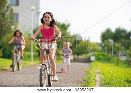 Three Happy Children Riding On Bicycle