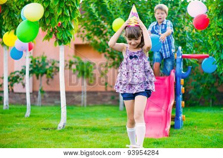 Two Happy Children Sliding At Playground