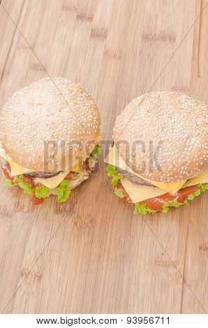 Two tasty cheeseburgers with lettuce beef double cheese and ketchup. Shallow focus.