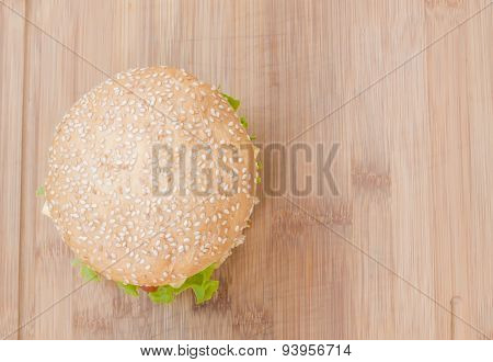 Tasty cheeseburger with lettuce beef double cheese and ketchup. From above view as background.