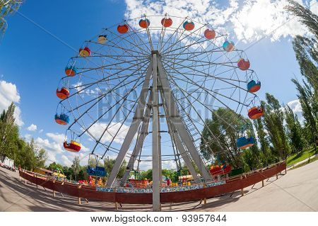 Ferris Wheel Against Blue Sky Background In City Park