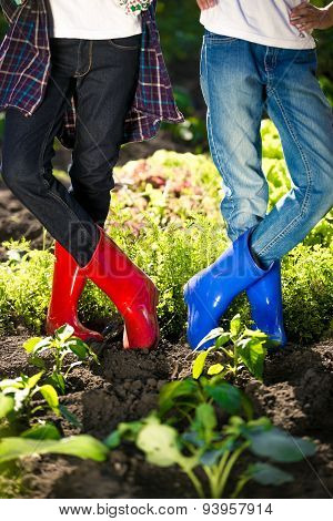 Two Girls In Gumboots Posing On Garden Bed At Hot Summer Day