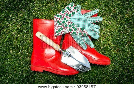 Closeup Photo Of Garden Tools And Red Gumboots Lying On Grass