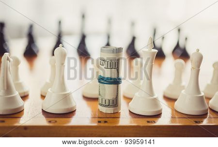 Toned Photo Of Twisted Money On Board In Place Of Chess Piece