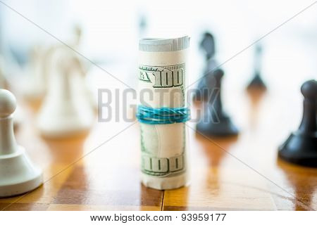 Closeup Of Twisted Dollars Lying On Wooden Chess Board
