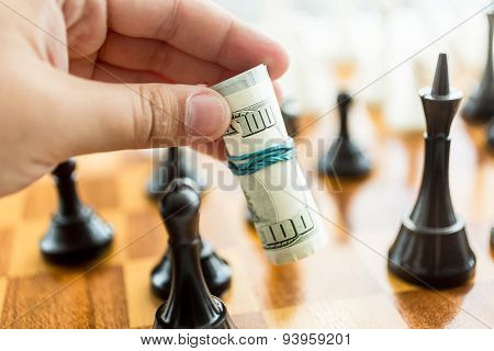 Conceptual Photo Of Man Making Move At Chess Game With Dollar Bills
