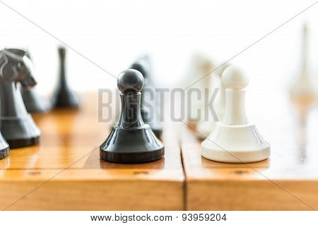 White And Black Pawns Standing In Front Of Each Other On Wooden Board