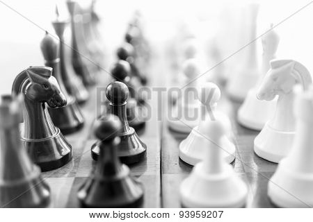 Black And White Shot Of Chess Pieces Standing In Rows Face To Face