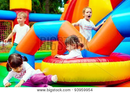 Happy Kids, Having Fun On Inflatable Attraction Playground