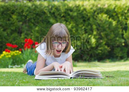 Girl Reading A Book In A Garden