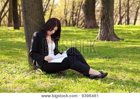 The Businesswoman Sitting On A Grass, Reading A Book