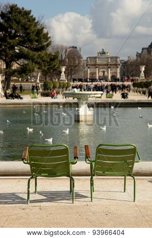 2 green and empty chairs at the Grand Bassin Rond in the Tuileries Garden, in Paris, France