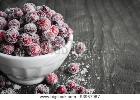 Sugared cranberries holiday dessert in bowl on rustic wooden background with copy space