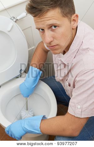 Portrait Of Unhappy Man Cleaning Toilet