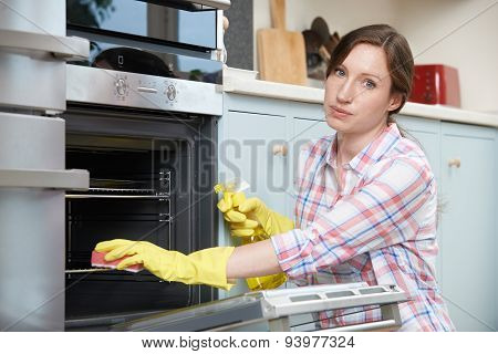 Portrait Of Fed Up Woman Cleaning Oven