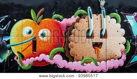 MOSCOW - JUNE 21, 2015: Graffiti on a urban wall (near B. Novodmitrovskaya street). Apple and cookies as a cartoon character.