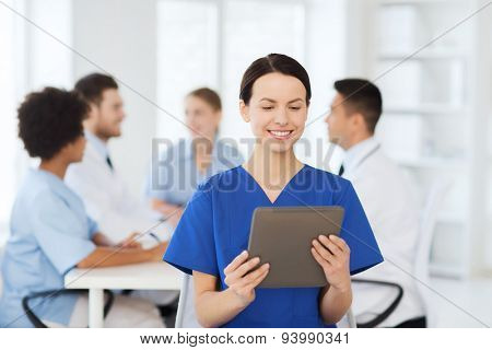 clinic, profession, people and medicine concept - happy female doctor with tablet pc computer over group of medics meeting at hospital