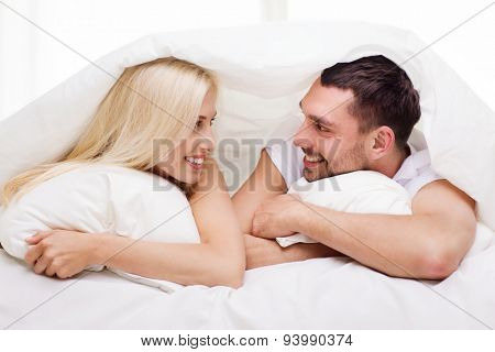 people, family, bedtime and happiness concept - happy couple lying in bed covered with blanket over head and talking at home