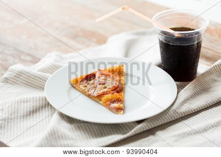 fast food, italian kitchen and eating concept - close up of pizza slice with cup of cola drink on wooden table