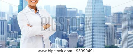 health care, science, people and medical concept - happy african american female doctor in white coat over city background