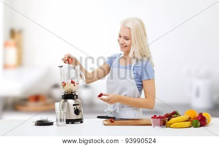 healthy eating, cooking, vegetarian food, dieting and people concept - smiling young woman putting fruits and berries for fruit shake to blender shaker over kitchen background