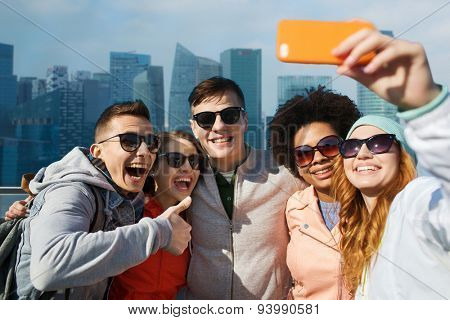 people, travel, tourism, friendship and technology concept - group of happy teenage friends taking selfie with smartphone and showing thumbs up over singapore city background