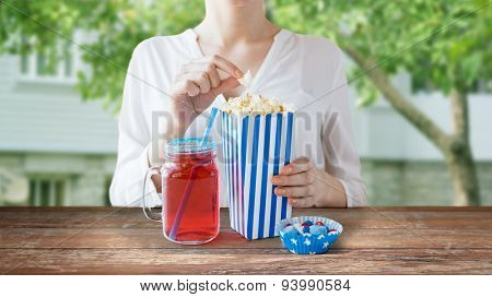 american independence day, celebration, patriotism and holidays concept - close up of woman eating popcorn with drink in glass mason jar and candies at 4th july party over summer house background