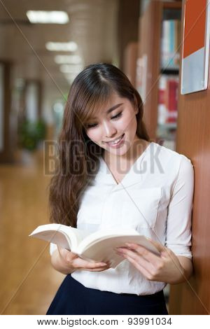 Asian beautiful female student look at book in library