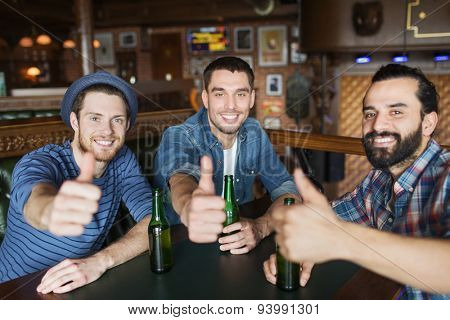 people, leisure, friendship, gesture and bachelor party concept - happy male friends drinking bottled beer and showing thumbs up at bar or pub