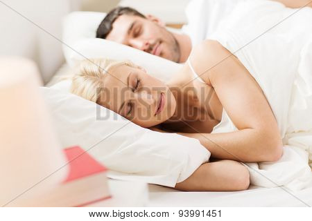 people, family, bedtime and happiness concept - happy couple sleeping in bed at home
