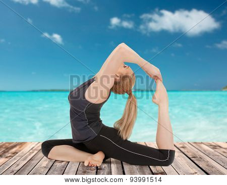 people, health, wellness and sport concept - happy young woman in one-legged king pigeon yoga pose on wooden floor over sea and blue sky background