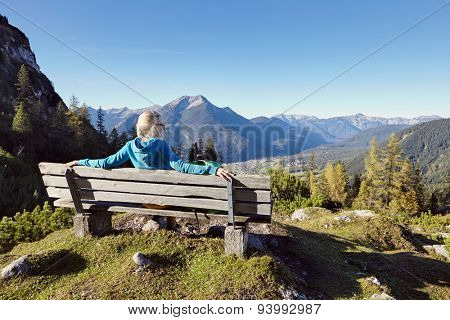 Rear view of blonde female hiker resting on wooden bench with view at beautiful mountain landscape