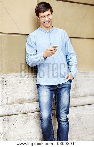 Attractive smiling young man in glasses and blue shirt with hand in pocket of jeans leaning on stone wall reading message on smartphone