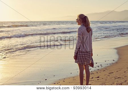 Young blonde woman in glasses and plaid dress with shoes in hand walking barefoot on wet sand of misty beach
