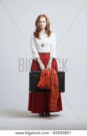 Young woman in vintage red skirt with a suitcase