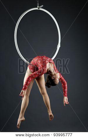 Beautiful aerialist doing acrobatic stunt on hoop