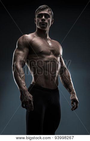 Handsome Muscular Bodybuilder Posing Over Black Background